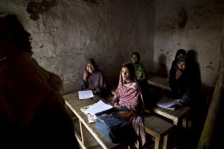 Refugiados afganos y desplazados internos niñas de la escuela paquistaní ríen con su maestro durante un examen en una escuela improvisada en las afueras de Islamabad, Pakistán, Viernes, 19 de diciembre 2014, días después de los combatientes talibanes murieron 148 personas - la mayoría de ellos niños - en una escuela masacre. (Foto por Muhammed Muheisen / AP Photo)