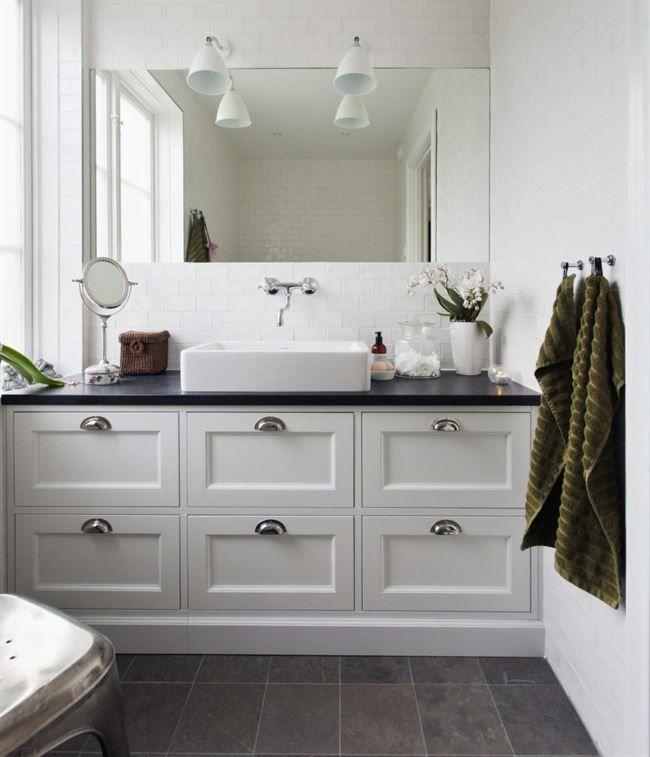 Inredningen i badrummet är byggt av Kungsäter kök exklusiv med fronterna Gårdshorn i vitt och beslag från Ett vackert kök. Handfat, Duravit, blandare, Badex. Lamporna Bestlite kommer från Gubi.