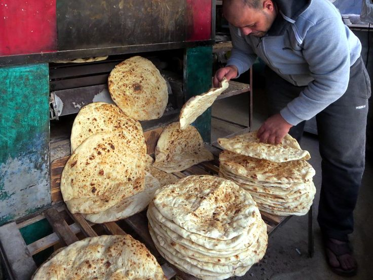 A baker at Dhiban south of Amman, Jordan, collects bread from his oven.