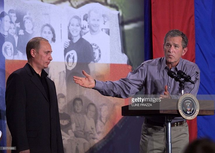 US President George W. Bush (R) speaks to students regarding his meeting with Russian President Vladimir Putin (L) during press conference at Crawford High School in Crawford, Texas 15 November 2001. Presidents Putin and Bush spoke to the students about the three-day meeting in which they discussed the down sizing of both countries nuclear arsenel. AFP PHOTO/Luke FRAZZA