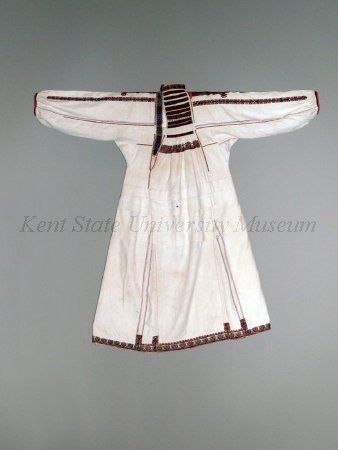 Romanian, Oltenia, Gorj or Ilfov  Description White cotton plain weave blouse chemise, embroidered with multicolor wool in smock and count stitches, long sleeves, smocked yoke, off center opening, ankle length, three tucks at waist.