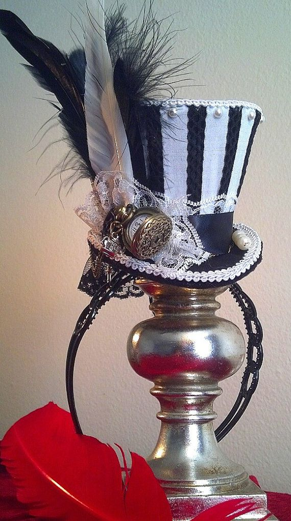 Humbug style of black and white stripes. Inspired Alice in Wonderland, Dark Alice McGee mini top hat also Night Circus (as we can add in red feather or ribbon rose) Feathers, hat pin, beading and a working mini pocket watch, We have added victorian key fob on the watch chain, and a teapot and cup charm. The hat is on hair band but can be changed to a hair clip.  We can work with your custom designs, please inquire. Feathers, Hat pin, design, beads can vary slightly Perfect for Wedding…