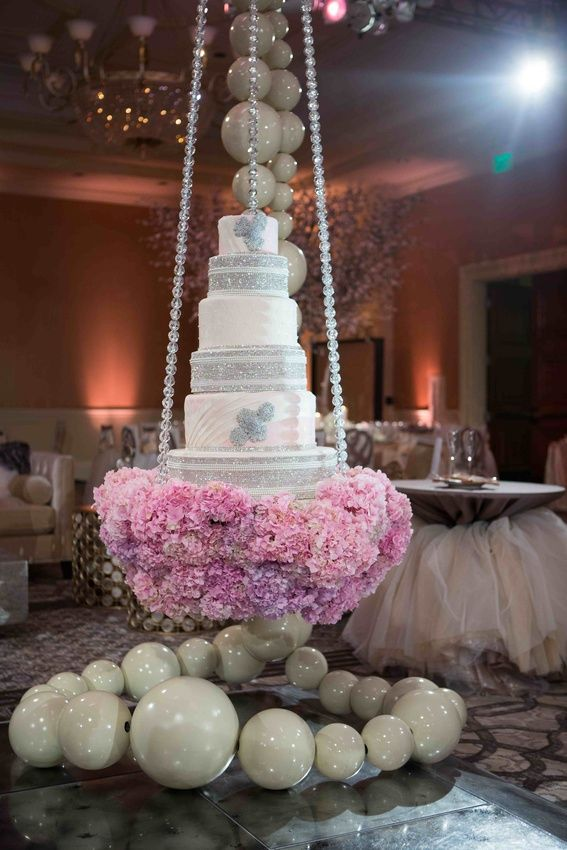 Celebrities Tamra Barney and Eddie Judge's tall wedding cake was displayed on a stand covered with pink hydrangeas that was suspended from the ceiling by crystal chains. The cake featured five ivory and blush tiers adorned with crystals. #ModernWeddingCake  Photography by: Christine Bentley Photography.