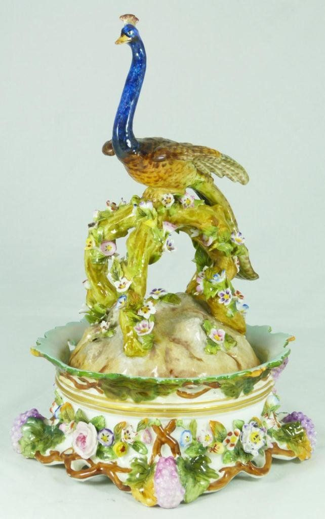 An antique German porcelain inkwell set having a figural peacock perched on branches with flowers over earth form base design to cover. Interior holds 3 pins and three inkwell inserts. Exterior of base has flower and grape cluster design. Each holds blue underglaze Crossed swords mark. 19th century.