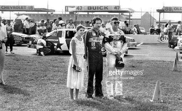 NASCAR drivers Dale Earnhardt (center) and Bobby Allison (right) and Earnhardt's wife, Teresa, stand near the race cars during opening ceremonies for the 1986 Firecracker 400 on July 4, 1986 at the Daytona International Speedway in Daytona Beach, Florida.