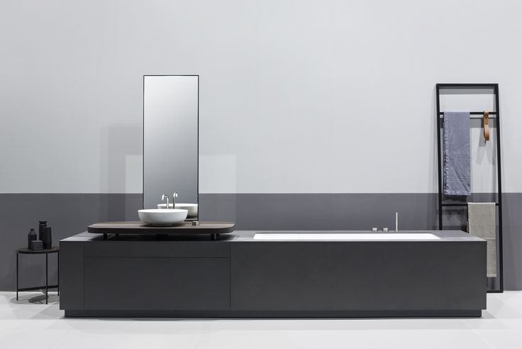 MANHATTAN is an integrated Bathtub Washbasin system in grey ecocement with an innovative console in smoked oak. It is also characterized by a refined graphic combination of lines and geometries, highlighted by the vertical mirror, the OX taps in stainless steel 316L and the open racks on both sides.