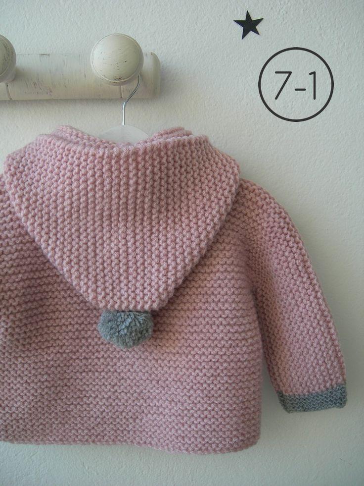 Cazadora para bebe hecho a punto bobo en rosa palo con capucha. Puños y pompón de capucha en gris plata y pompones de distintos colores en cremallera. Interior en lunares.