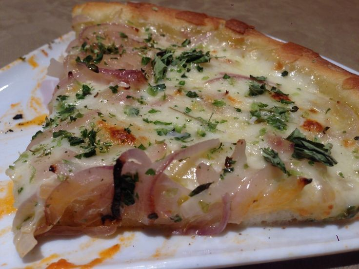 Receta casera para preparar la pizza fugazza con queso, pizza de cebolla estilo argentino con mozzarella.
