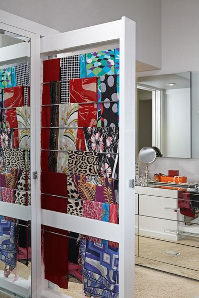 A double-sided, pull-out cabinet is a space-saving way to hang scarves. The concept of using rods is helpful. People think to put scarves in a drawer or a basket.  Why not use dowels or rods or a pull-out cabinet? You even could use a towel bar