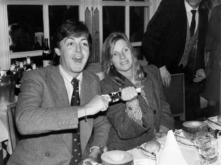 Paul and Linda McCartney, each pulling half of a holiday popper, must of been a Christmas celebration.