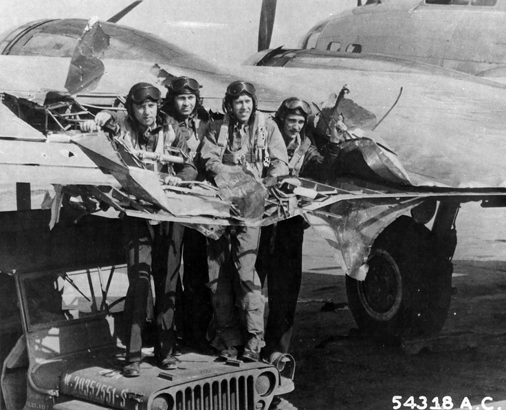 American crew demonstrates the size of a hole in the wing of a B-17, resulting from German flak during a raid on  Ludwigshafen, 1944. The B-17 was famous for sustaining crippling damage and still possessing the airworthiness to allow pilots to fly to safety.