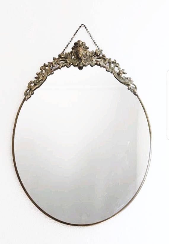Franse antieke koperen spiegel   ITEM ***  Deze spiegel met een ovale vorm heeft een prachtige barokke messing ontwerp op de top. Er is een vorm van het hoofd van een vrouw in het midden van het sieraad. Als je goed kijkt zie je de neus ontbreekt, ik denk dat dit de spiegel meer karakter geeft. De rand is ook gemaakt van messing.    AFMETINGEN ***  37 x 50 x 4 cm    VOORWAARDEN ***  De spiegel is in een uitstekende vintage staat, geen krassen of wat dan ook. Het sieraad heeft echter enkele…