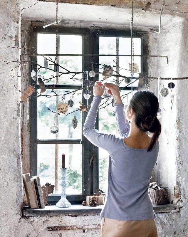 Voeg een natuurlijk kerst-effect toe aan de je ramen door er takjes voor te hangen die je dan decoreert met dennenappels en kerstballen.