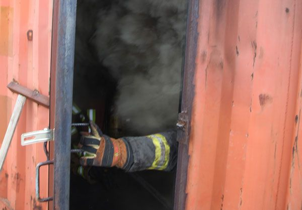 A firefighter emerges from a flashover simulator. Photo by Tony Greco.