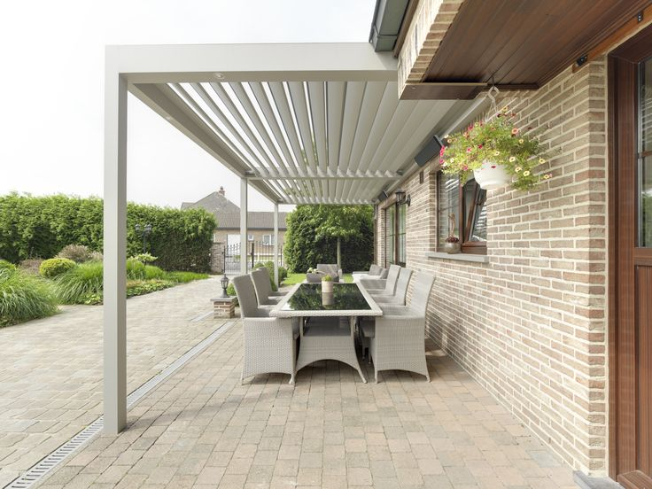 Umbris Patio Roof | automated louvre roof over patio of traditional brick home , aluminium legs support the roof and drain water. patio roof is fully watertight when louvres rotated flat