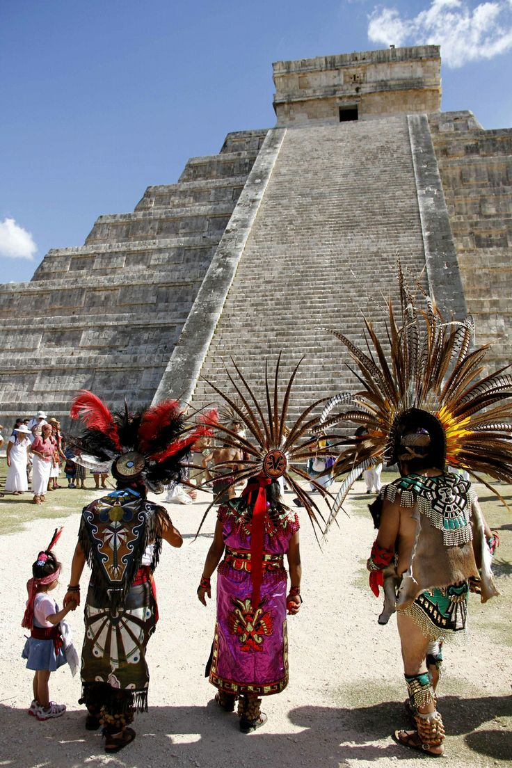 """Dancers perform in front of the Maya temple of Kukulkan (El Castillo) in Chichen Itza, Yucatan, Mexico. During the spring and autumn equinoxes, the late afternoon sun strikes off the northwest corner of the pyramid and casts a series of triangular shadows against the northwest balustrade, creating the illusion of a feathered serpent """"crawling"""" down the pyramid. [http://en.wikipedia.org/wiki/El_Castillo,_Chichen_Itza]"""