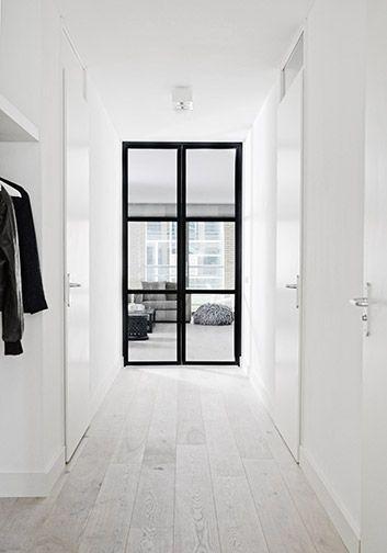 minimal black and white interior   white floors   black trim door