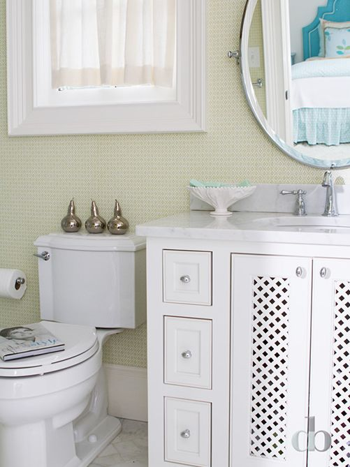 White and green kids' bathroom features walls clad in green diamond print wallpaper lined with an oval pivot mirror over a crisp white washstand fitted with lattice doors and topped with white marble next to a toilet under window.