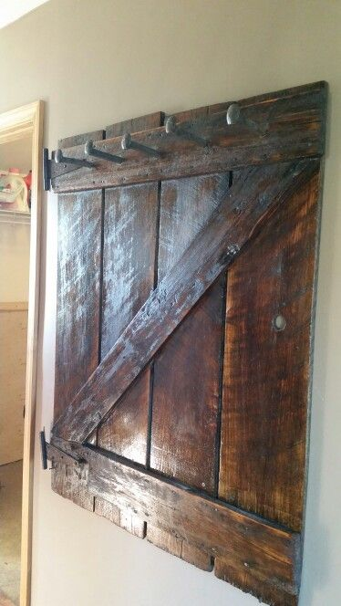 100 year old barn door made into a coat rack using railroad spikes.