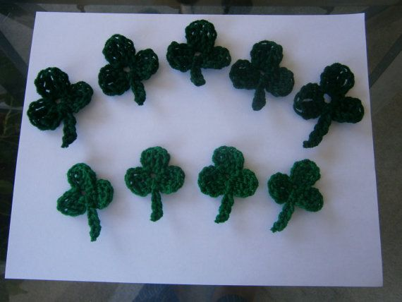 9 hand-crocheted Shamrock decorations. 5 dark green, 4 lighter green.