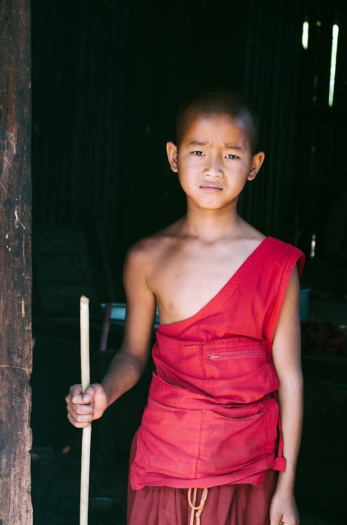 A young monk begrudgingly tend to the monastery fire in Shan State, Myanmar