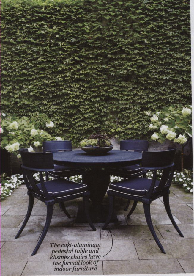 black outdoor dining table and klismos chairs in cast aluminum