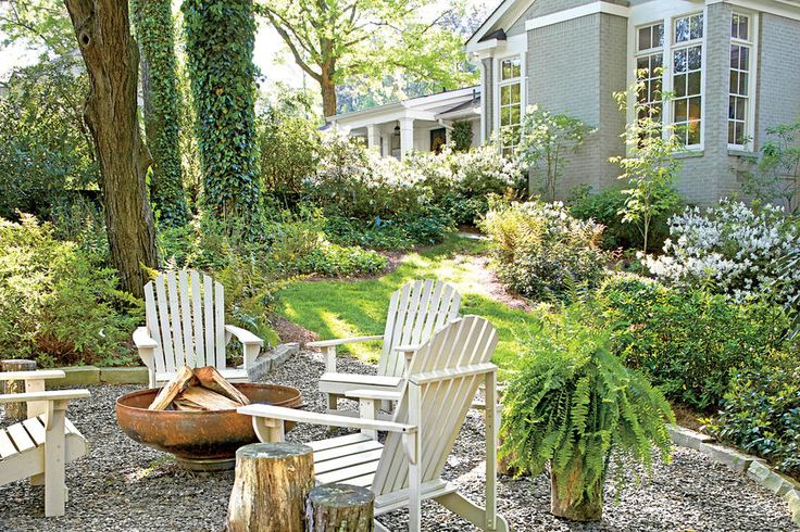 Now It's a Grown-Up Gathering Place - Before and After Yard Makeovers That Will Make Your Jaw Drop - Southernliving. Adirondack chairs, a gravel surface with a stone border, and a rustic metal fire pit makes the perfect spot for gathering on chilly evenings.