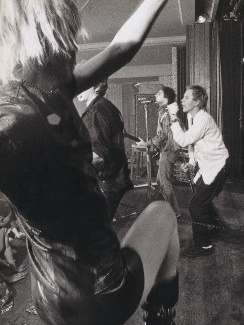 This shot was taken in the early days when the Sex Pistols could actually play gigs! Featured here are Steve Jones, Johnny Rotten and Glen Matlock and the lady in the foreground is  Vivienne Westwood dancing on stage with them. S)