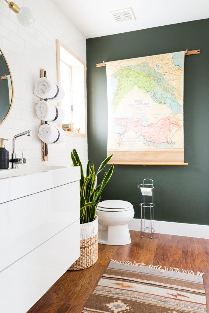 dark olive green wall + wood floor + ikea bathroom cabinet + rolled towel holder + plant in wicker basket + kilim