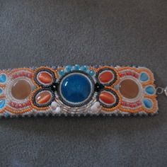 Bracelet manchette perles rocaille et cabochons blanc et orange