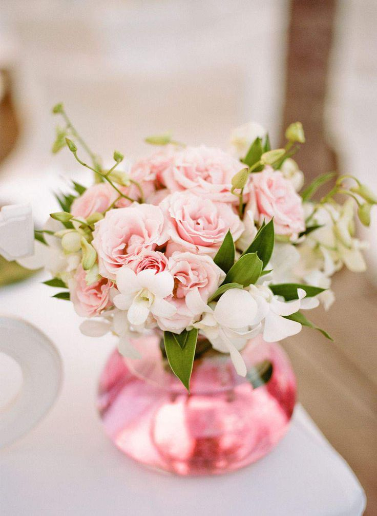 Mixture of red and blush roses and cream gardenias with greenery - similar vase, but clear. Jewels and petals sprinkled.