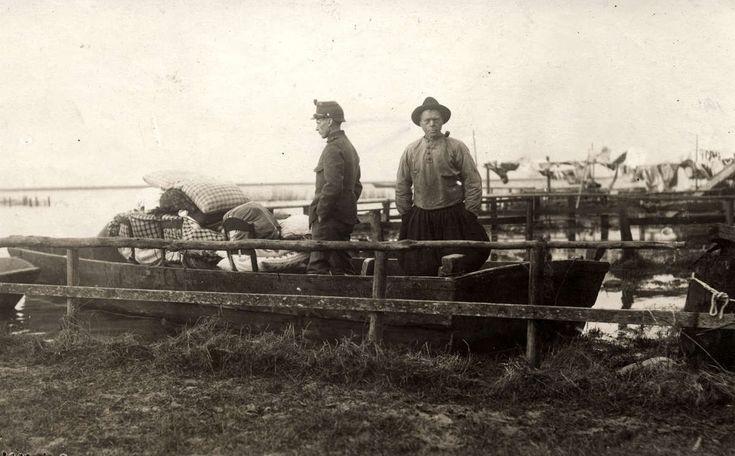 Overstroming, watersnood. Mannen in een boot met wat spullen die ze na de overstroming uit hun huizen  hebben kunnen redden. Nederland, Marken, 1916 #NoordHolland #Marken