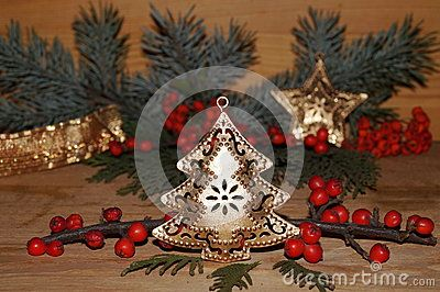 Christmas arrangement with gold christmas tree, gold star, red berries and  fir branches
