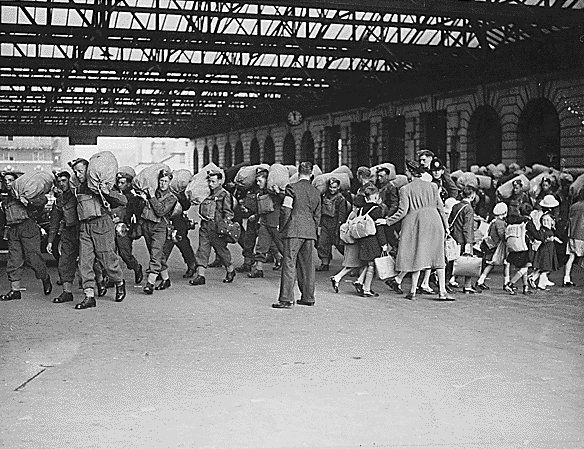 At a London railway station, arriving troops pass by children who are being evacuated to the countryside.