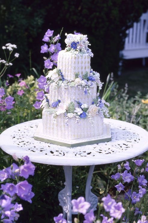All over texture and white sugar roses, Lily of the Valley and violets add detail to three layers of white hexagonal cake.