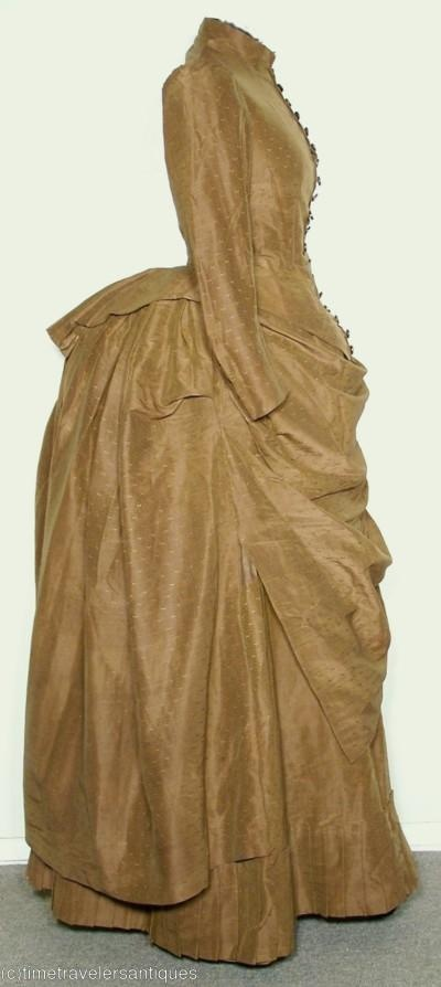 A most becoming original circa 1885 lady's rich golden brown silk brocade two piece bustle dress with a lined bodice having 18 matching ornate floral gold and silver colored glass buttons to the long front closure, and a double inverted pleated tail. The brown polished cotton lined skirt has an attached fashionable pleated draped overskirt, a pleated waterfall bustled back, and a complimenting pleated ruffled hem.