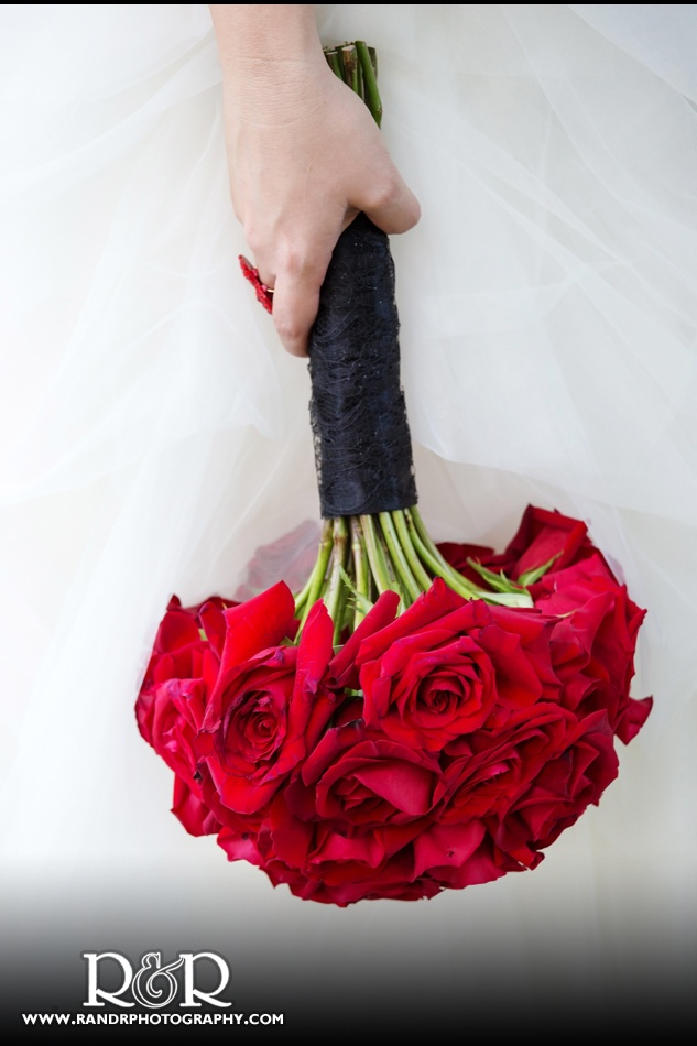 I like the idea of a red rose bouquet with black ribbon down the stems. Maybe add some white skinny ribbon too?
