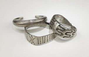 9-10th C. Found in Ireland. Silver armlet with overlapping ends and expanded centre with 6-pointed star of punched zigzags, a saltire on each terminal.