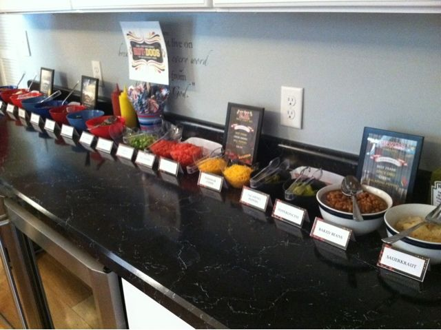 The Smart Momma: Hot Dog Bar Topping includes: Sauerkraut, Baked beans, cheddar cheese, chili, tomatoes, coleslaw, onions, jalapenos, salsa, red peppers, green peppers, green onions, pickles, and banana peppers (could add marinated eggplant, ketchup, mayo, relish, yellow mustard, Dijon or sweet mustard, bacon...)