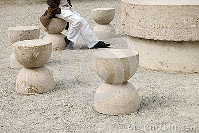 Man sitting at the Table of Silence, the famous expressionist sculpture by Constantin Brancusi. In Targu Jiu, Romania.
