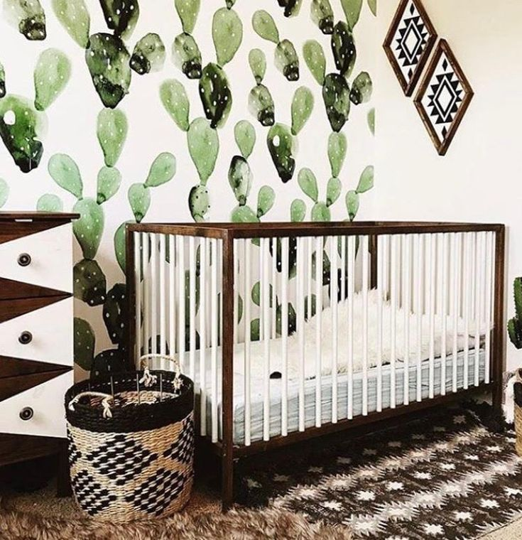 Bohemian style nursery with cactus-patterned wallpaper.