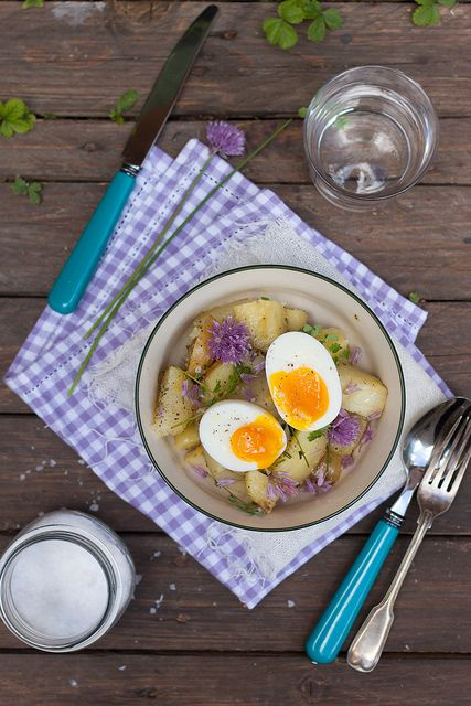 An elegant Spring potato salad with chives flowers and soft boiled eggs