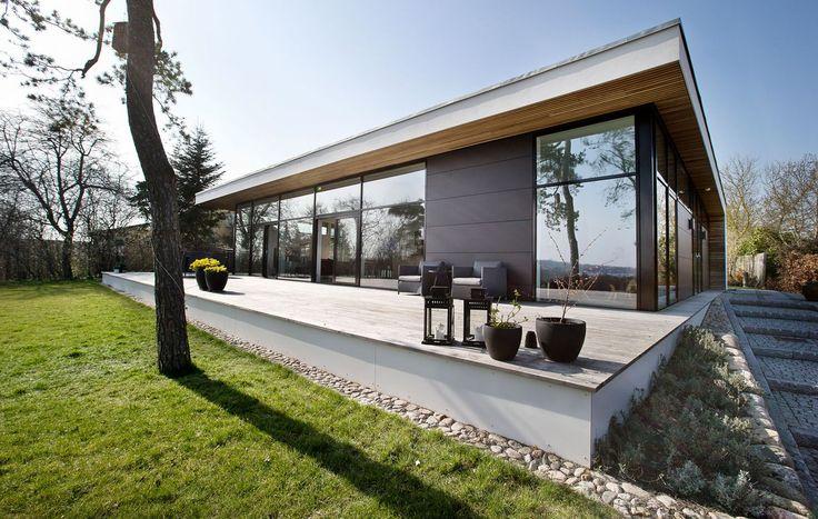 En enkelt og stilren terrasse skaber en elegant uderum til villaen ...