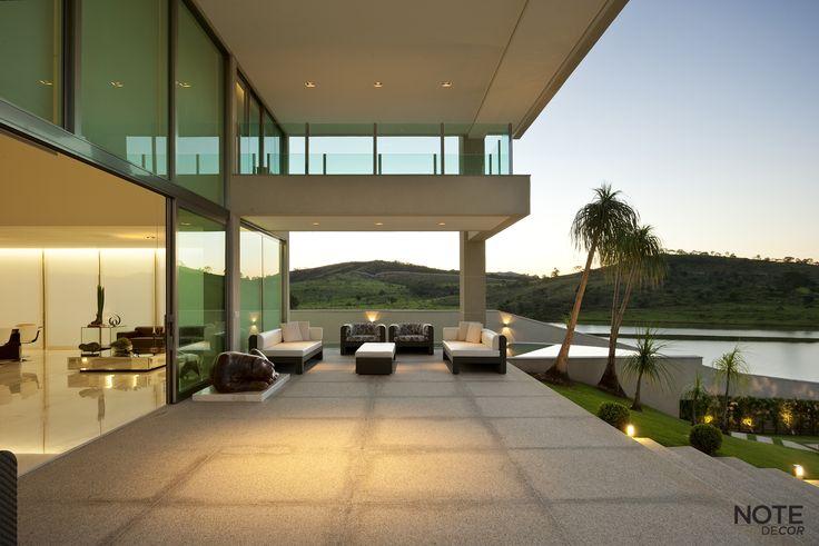 A Varanda conta com um projeto de iluminação específico para deixar o clima mais acolhedor.   Residência Aldeias do Lago, Nova Lima - BH  Projeto: Myrna Porcaro