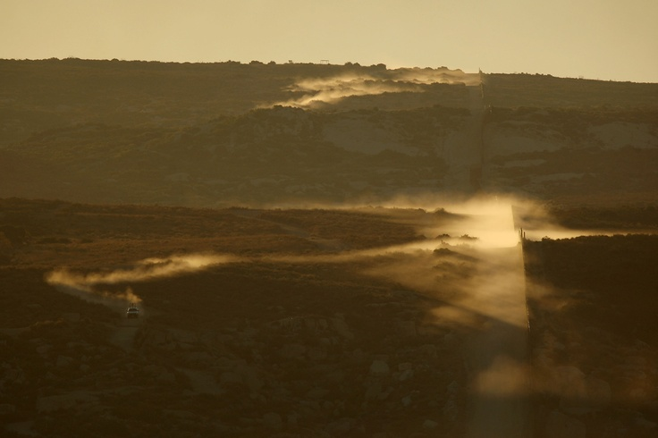 Clouds of dust kicked up by border patrol vehicles hang in the air along the US-Mexico border fence as agents carry out special operations on July 30, 2009 near the rural town of Campo, some 60 miles east of San Diego. (David McNew/Getty Images)