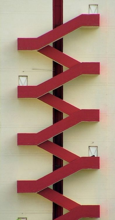 Red exterior stairs, white wall. Fire Escape.