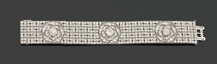 BEAUTIFUL BRACELET articulated ribbon accented with three diamonds brightened in crimp in a setting of roses repercées and set with diamonds and brightened decor brightened braces also paved diamonds. Platinum setting. Years of work in 1925. Weight of the three main diamonds: 1,20 - 1.20 to 1.25 carats each about (TA). Dimensions: 16.7 x 2.2 cm. Ref: For a tiara with the same decor rosettes and grid, see page 84, Boucheron, Ed Port-Royal, 1988. Gilles NERET.