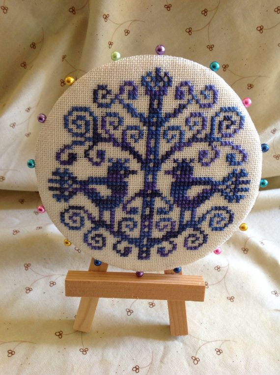 Cross stitched jewel toned blue bird pin keep.