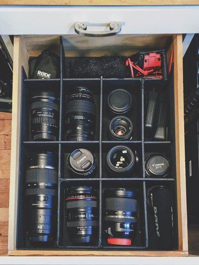 Camera equipment storage and organization - old shelf converted into easy lens and camera equipment storage by making compartmentalized spaces for each piece of gear.