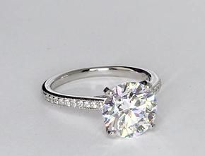 Elegant with a touch of vintage, this diamond engagement ring setting features pavé-set diamonds in a delicate platinum milgrain design to frame your center diamond. 1/8 carat total diamond weight.